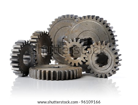 Old worn cog gear wheels on white reflective background. - stock photo