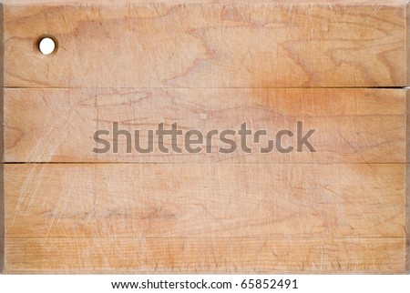 Old worn, cracked and scratched wooden cutting board. - stock photo