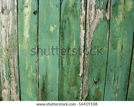 old worn down and peeling away green painted wooden fence panel - stock photo