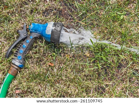 Old worn garden hose spray gun running water on green and dry grass, top down view. Abandoned sprayer spraying a stream of water and bubbles on a thirsty lawn.   - stock photo