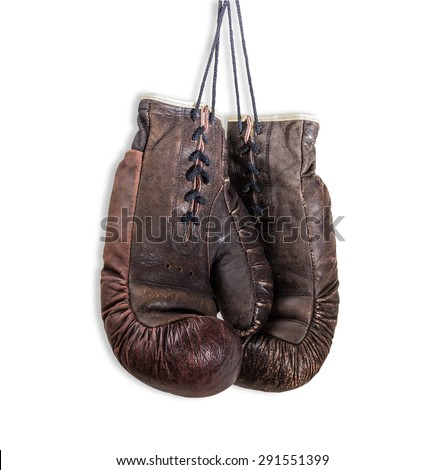 Old worn leather brown boxing gloves, that hang on a laces. Isolation on a light background. - stock photo