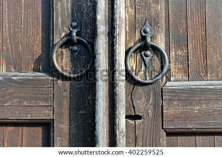 Old worn metal door handles in the form of ring at the timbered weathered door with keyhole. Architectural background. Retro filter applied.  - stock photo