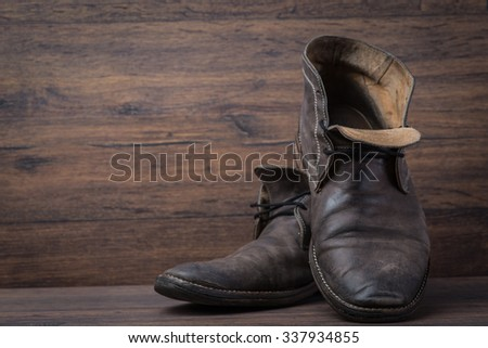 Old worn out brown leather shoes over the brown background - stock photo