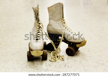 Old worn roller skates with big shoe-laces - stock photo