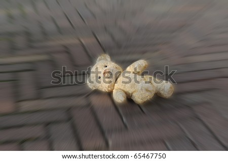 Old worn teddy bear lost on the street - stock photo