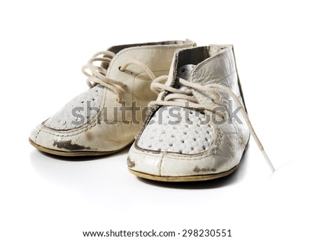 Old worn vintage leather white baby shoes isolated on white with natural shadows. - stock photo