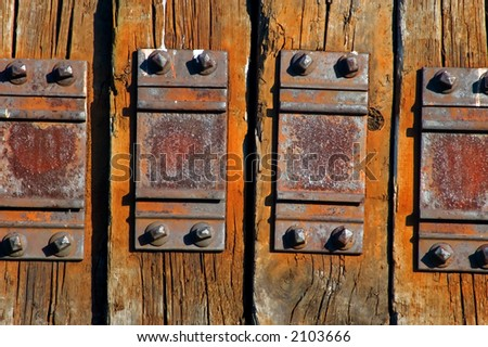 old worn wooden wall with metal plates