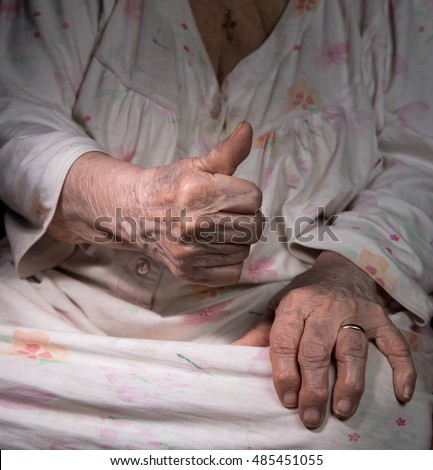 Old wrinkeld woman's hand with thumb up. Old woman showing ok sign