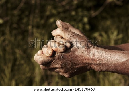 old wrinkled hands.  farmer prays at farm.  - stock photo