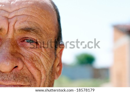 Old wrinkled man with blurry background - stock photo