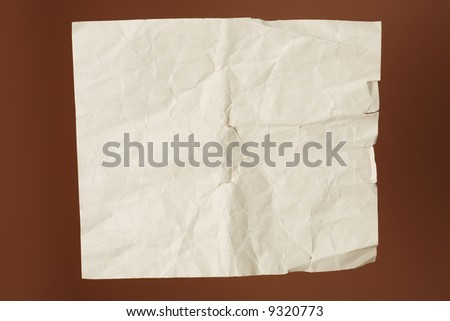 Old wrinkled paper on brown background