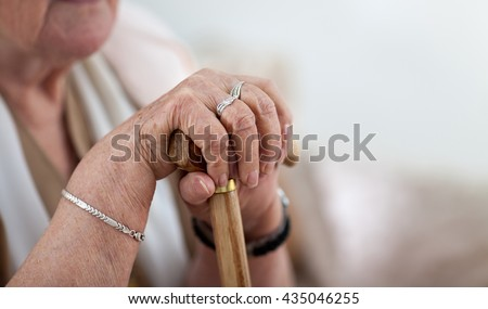 Old wrinkled woman hands holding walking stick - stock photo