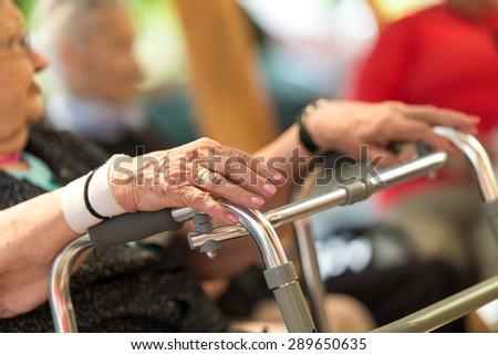 Old wrinkled women hand hold walker - stock photo