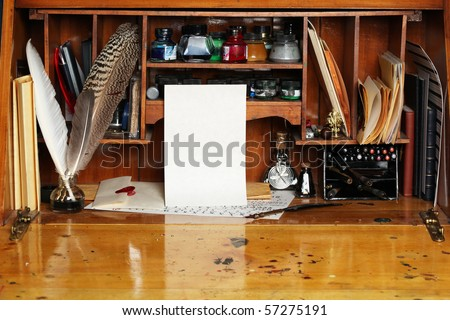 Old writing desk full of quills & inks for calligraphy - stock photo