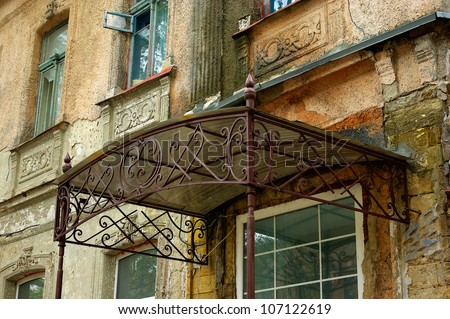 old wrought-iron canopy over the door of an old house