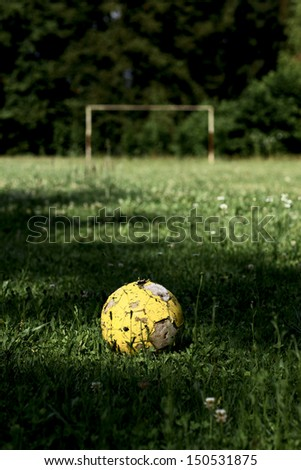 Old yellow ball on soccer field  - stock photo