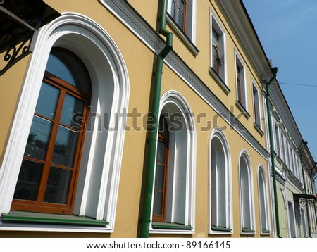 old yellow building with green storm-down pipe at day - stock photo