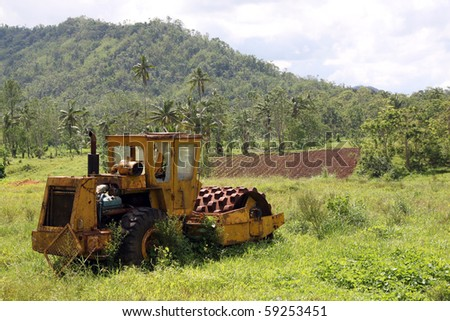 Old yellow buldozer on the green grass foe sell
