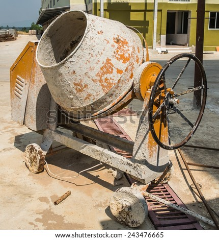 Old Yellow Cement Mixer outdoor in building site - stock photo