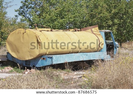 Old yellow dilapidated abandoned truck - stock photo