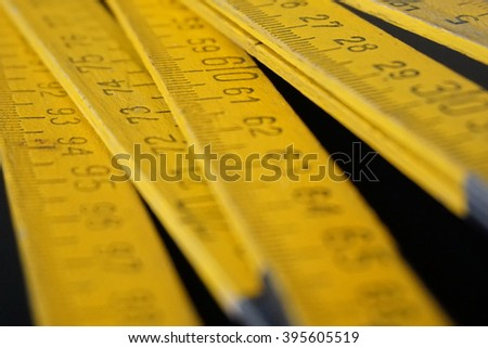 Old yellow folding meter ruler measuring centimeters on the black surface - stock photo