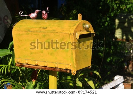 old yellow mail box in garden - stock photo