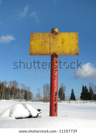 old yellow metal sign on blue sky background - stock photo