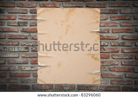 Old yellow paper on brick wall. - stock photo