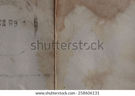 Old yellow paper with stains and postmark stamp smudges. Background texture grungy design element. - stock photo