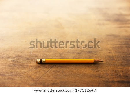 Old yellow pencil on a old used wooden desk.  - stock photo