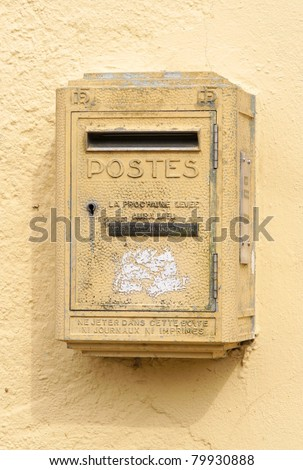 old yellow postoffice box hanging on a wall - stock photo