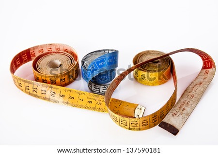 old yellow red blue measure tapes rolled - stock photo