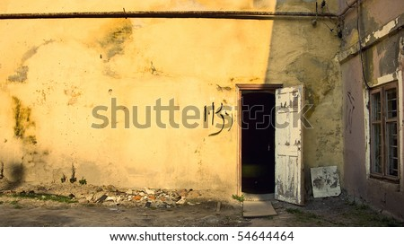 Old yellow rough wall and open door