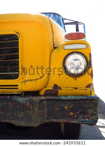 Old yellow school bus with chipped paint and rust - stock photo
