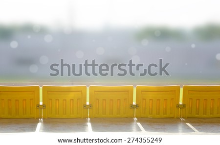 Old yellow seats  in the stadium under the sunlight in the morning. - stock photo