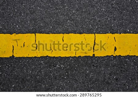 Old yellow traffic lines on the road. - stock photo