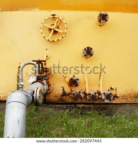 old yellow wall of the fuel tank to an oil storage equipment and pipe - stock photo