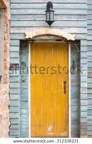 Old yellow wooden door with sign and lamp on blue wall vintage style - stock photo