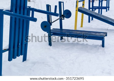 Old yet still functional soviet style outdoor gym painted in blue paint with fresh winter snow - stock photo