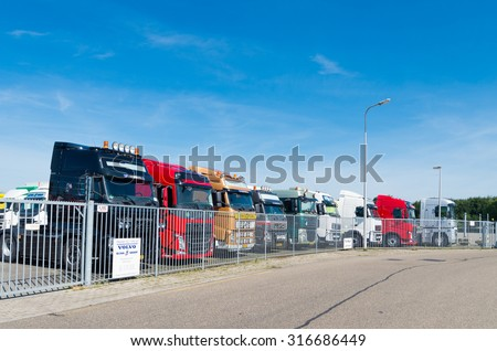OLDENZAAL, NETHERLANDS - AUGUST 1, 2015: Row of used volvo trucks for sale behind a gate.  Volvo is the world's second largest heavy-duty truck brand. - stock photo