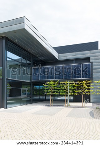 OLDENZAAL, NETHERLANDS - AUGUST 10, 2014: Solar panels above the entrance of a modern office building - stock photo