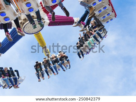 OLDENZAAL, NETHERLANDS - SEPTEMBER 28, 2014: Unknown adolescents enjoying their ride in a fair attraction - stock photo