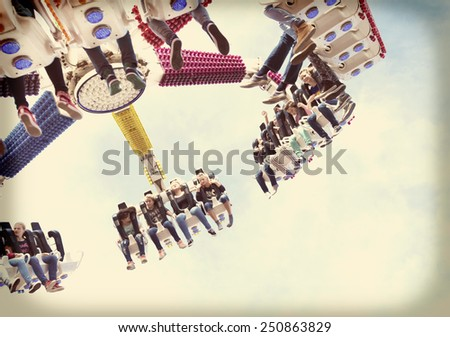 OLDENZAAL, NETHERLANDS - SEPTEMBER 8, 2014: Vintage filtered image of unknown adolescents enjoying their ride in a fair attraction - stock photo