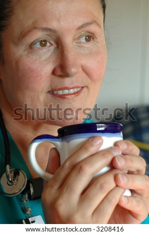 Older, attractive nurse enjoying a cup of coffee during her break - stock photo
