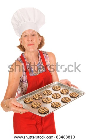 older attractive woman in red apron and white chefs hat holding a tray of cookies - stock photo