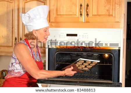 older attractive woman in red apron and white chefs hat removing a tray of cookies from oven - stock photo