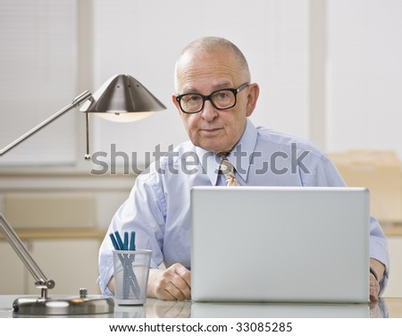 Older bald man with glasses on laptop. Desk lamp lighting from above. Horizontal. - stock photo