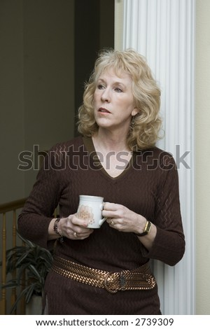 Older blond woman leaning against a column enjoying a cup of coffee