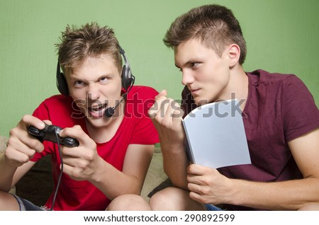 Older brother cant study from the noisy young brother who plays video game - stock photo