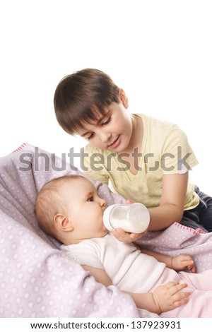 Older brother feeds his little sister from the milk bottle isolated on white background - stock photo